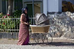Dam med gammal barnvagn